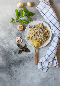Domowy włoski makaron fettuccine z grzybami i sosem śmietanowym podany na białym talerzu z bazylią (fettuccine al funghi porcini). tradycyjna kuchnia włoska. szare tło, widok z góry, miejsce