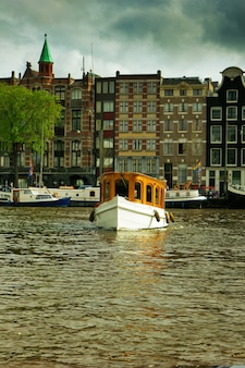Domy i łodzie na kanałach amsterdamu, holandia. hdr