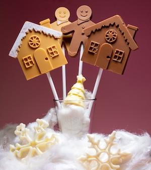 Domy i ludzie z czarnej i mlecznej czekolady na patyku