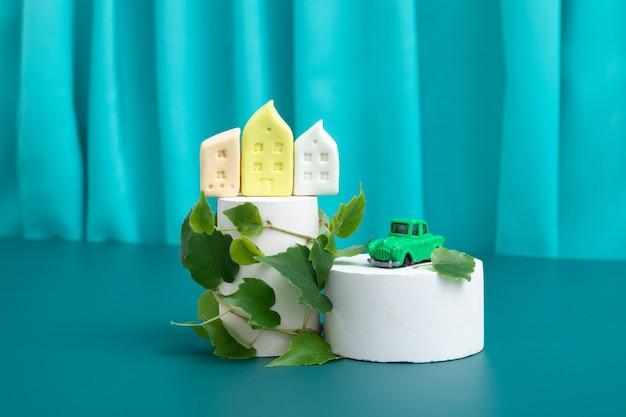 Domy i samochód na podium lub podeście z zielonymi liśćmi roślin - symbol ekologicznej zabudowy lub budownictwa