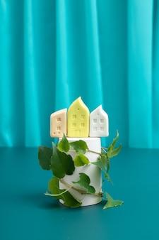 Domy na podium lub podeście z zielonymi liśćmi roślin - symbol ekologicznej zabudowy lub budownictwa