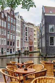 Domy na wodzie w amsterdamie. stoliki w kawiarni na moście. świetny pejzaż miejski. pionowy.