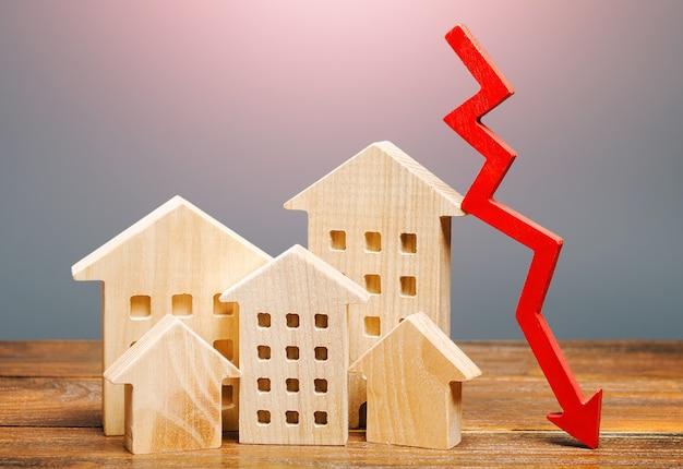Domy nieruchomości i czerwona strzałka w dół