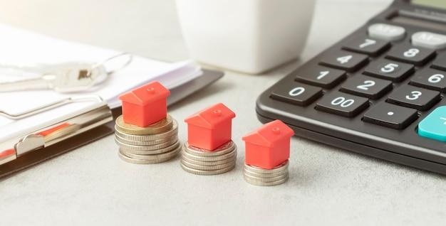 Domy spoczywające na stosach monet funtowych obok kalkulatora