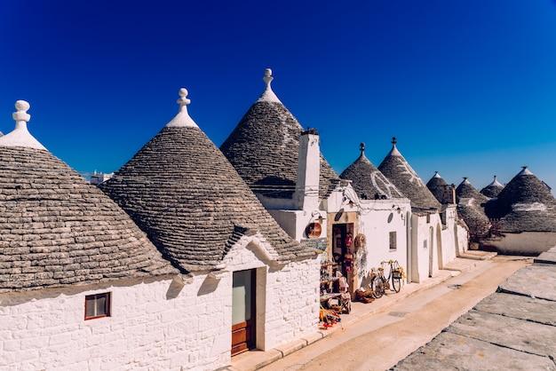 Domy turystycznego i słynnego włoskiego miasta alberobello, z typowymi białymi ścianami i stożkowymi dachami trulli.