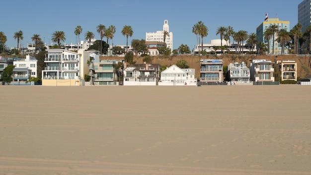 Domy weekendowe przy plaży i piasku. budynki nad brzegiem morza na plaży santa monica, kalifornia, usa.