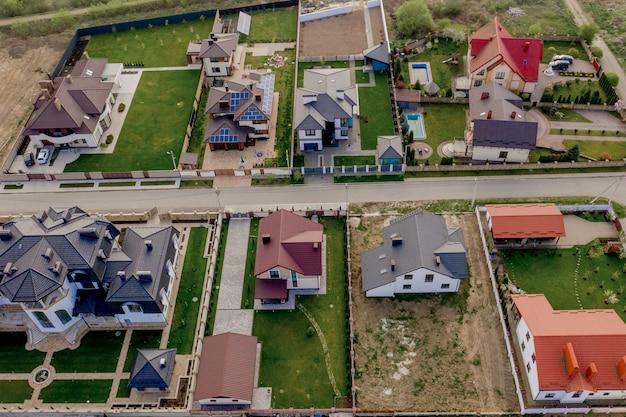 Domy z utwardzonymi podwórkami i trawnikiem z zieloną trawą