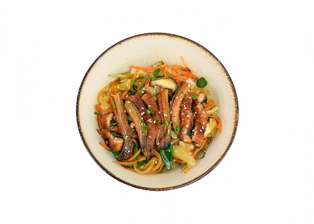 Donburi unagi lub plastry węgorza z ryżem, warzywami w ceramicznej misce