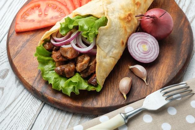 Doner kebab leży na desce do krojenia. shawarma z mięsem, cebulą, sałatką leży na białym starym drewnianym stole.