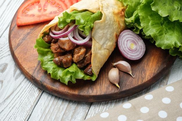 Doner kebab leży na desce do krojenia. shawarma z mięsem, cebulą, sałatką leży na ciemnym starym drewnianym stole.
