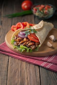 Doner kebab leży na desce do krojenia. shawarma z mięsem z kurczaka, cebulą, sałatką leży na ciemnym starym drewnianym stole.