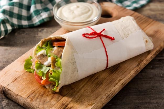 Doner kebab lub shawarma kanapka na drewnianym stole.