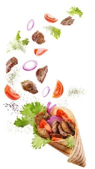Doner kebab lub shawarma z unoszącymi się w powietrzu składnikami: mięso wołowe, sałata, cebula, pomidory, przyprawy.