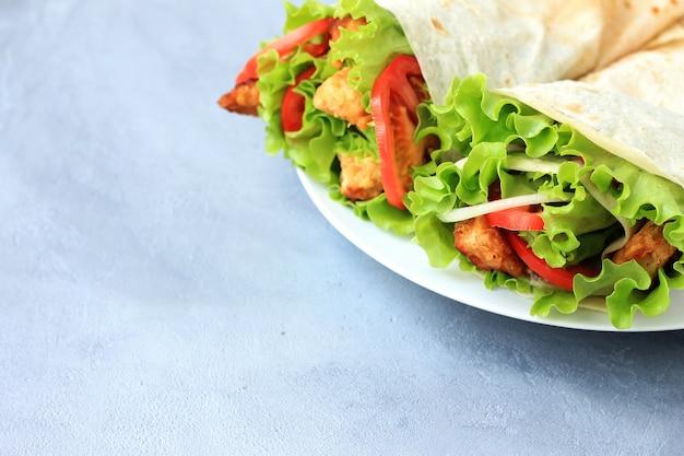 Doner kebab na białym talerzu. shawarma z mięsem, cebulą, sałatką i pomidorem na szarym tle.