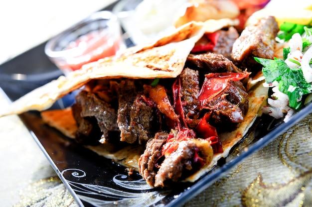 Doner kebab na drewnianym tle z pomidorami i zieleniami.