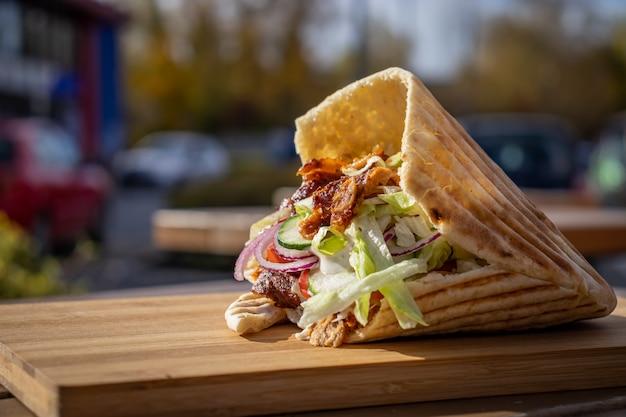 Doner kebab na lokalnym straganie z ulicznym jedzeniem na drewnianej desce do krojenia