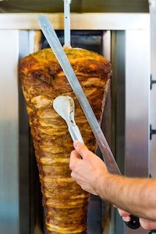 Doner kebab - przyjazny sprzedawca w tureckiej knajpce fast food, krojenie mięsa ostrym nożem przed szpikulcem