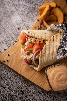 Doner kebab shawarma w dole świeżych warzyw i mięsa