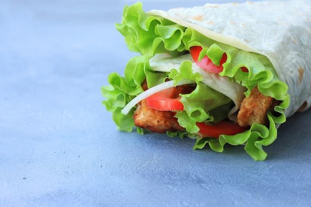 Doner kebab. shawarma z mięsem, cebulą, sałatką i pomidorem na szarym tle.