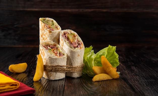 Doner kebab, shawarma z rustykalnymi ziemniakami i kapustą na drewnianym teksturowanym tle