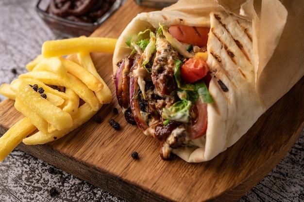 Doner kebab to shawarma w dołku ze świeżych warzyw i mięsa z dużymi przyprawami restauracja serwująca...