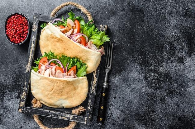 Doner kebab z grillowanym mięsem z kurczaka i warzywami w chlebie pita na drewnianej tacy na drewnianym stole. widok z góry.