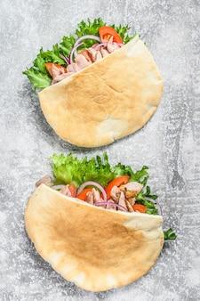Doner kebab z grillowanym mięsem z kurczaka i warzywami w pita na szarości. widok z góry.