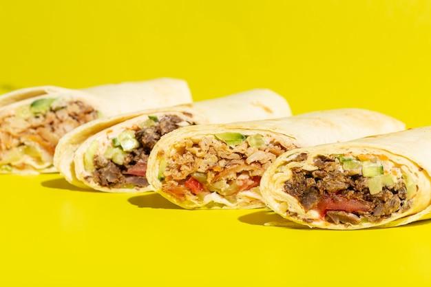 Doner roll shawarma z kurczakiem i warzywami na żółtym wysokiej jakości zdjęciu