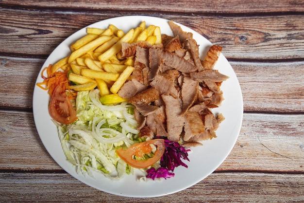 Doner wołowy na talerzu z frytkami i sałatką na drewnianym stole