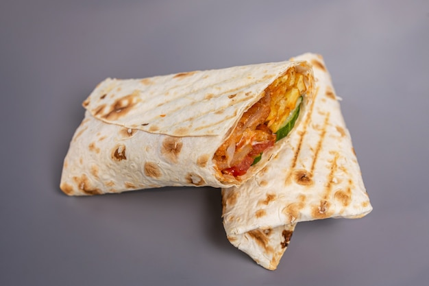 Donery w chlebie pita w kawałku na szarej powierzchni.