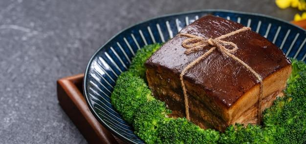 Dong po rou (mięso wieprzowe dongpo) na pięknym niebieskim talerzu z zielonymi warzywami brokułowymi