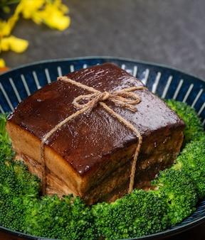 Dong po rou (mięso wieprzowe dongpo) w pięknym niebieskim talerzu z zielonym warzywem brokuły, tradycyjne świąteczne potrawy na posiłek kuchni chińskiej nowego roku, z bliska.
