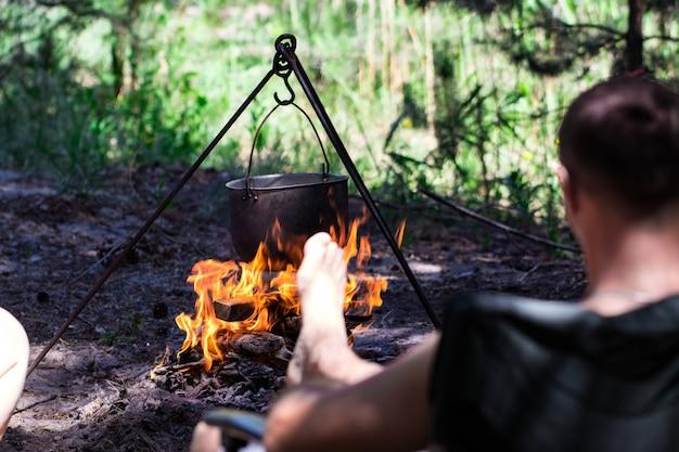 Donica turystyczna wisząca nad ogniem na statywie. gotowanie w kampanii.