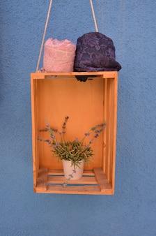 Doniczka na drewnianym pudełku, z niebieską ścianą.