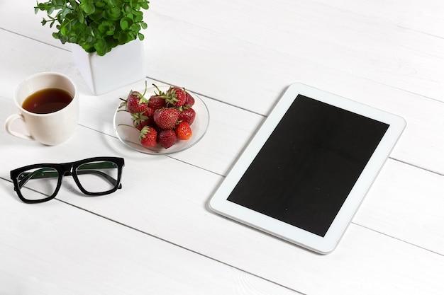 Doniczka, okulary, tablet na białym pulpicie. białe tło. widok z góry. skopiuj miejsce.