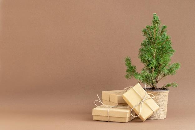Doniczkowa choinka z ekologicznymi pudełkami prezentowymi na brązowym tle