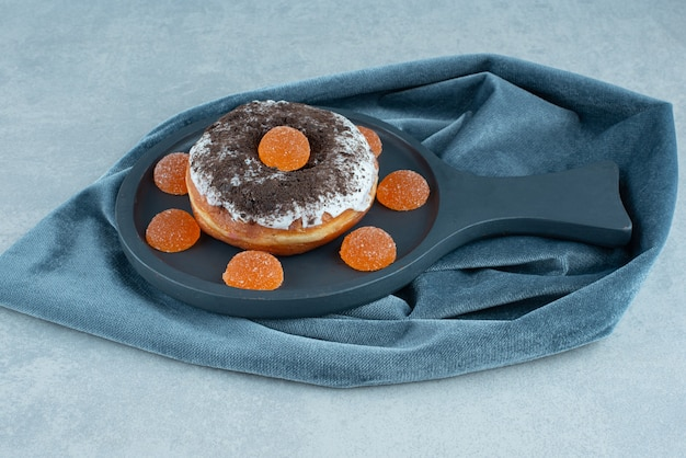 Donut zwieńczony i otoczony marmoladami na talerzu z marmuru.