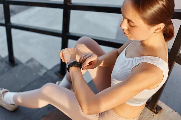 Dopasowana brunetka dziewczyna w białym topie i leginsach, siedząca na schodach i patrząca na zespoły fitness