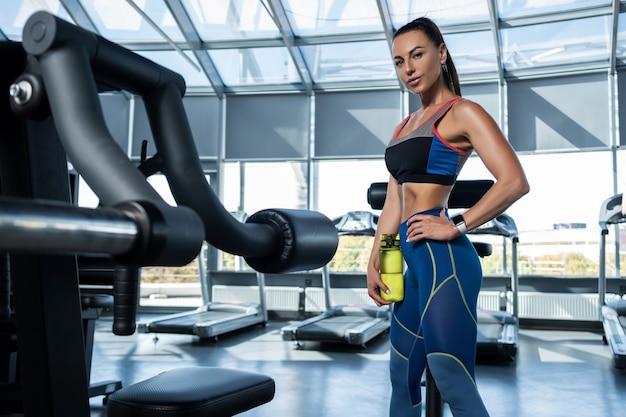 Dopasowana brunetka kobieta stojąca w siłowni trzymająca butelkę wody water