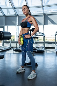 Dopasowana brunetka kobieta stojąca z butelką wody w siłowni