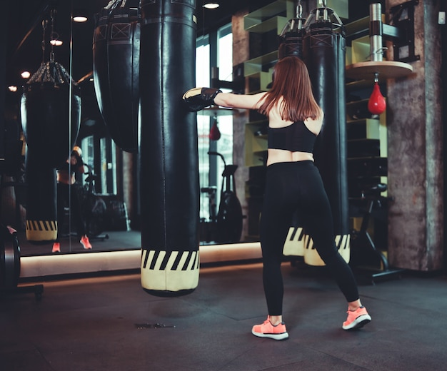 Dopasowana dziewczyna w strojach sportowych i rękawicach bokserskich trenuje uderzenie w worek treningowy w ciemnej siłowni