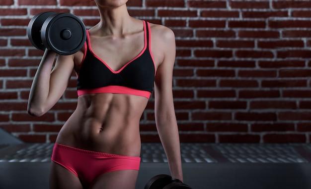 Dopasowana i stonowana kobieta trenująca na siłowni
