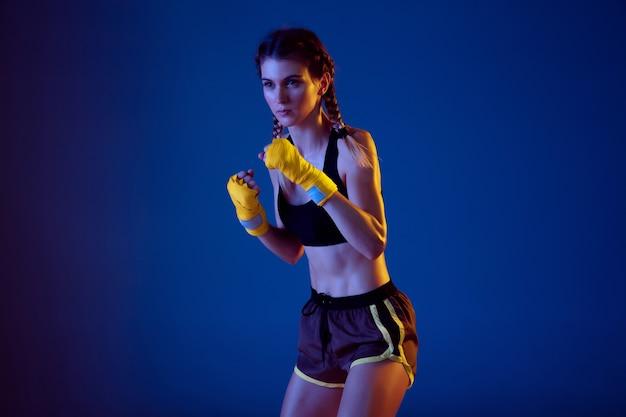 Dopasowana kaukaska kobieta w boksie w odzieży sportowej na niebieskim tle studia w świetle neonowym