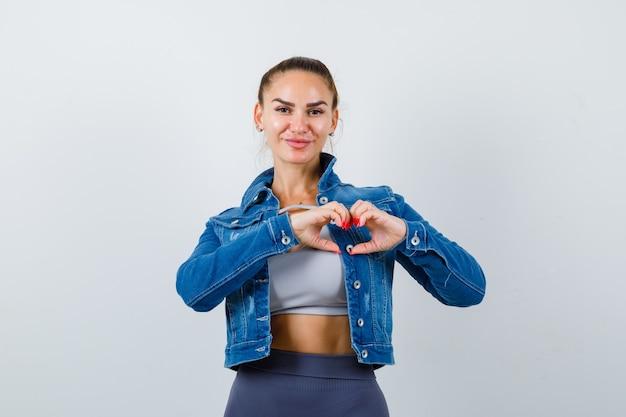 Dopasowana kobieta pokazując gest serca w crop top, kurtka dżinsowa, legginsy i patrząc szczęśliwy, widok z przodu.