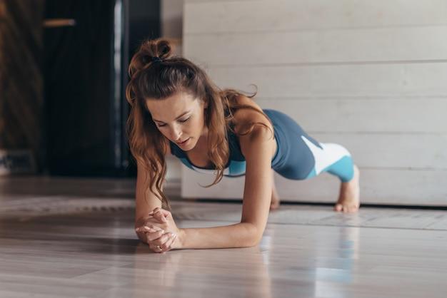 Dopasowana kobieta robi ćwiczenia deski, trening w domu.