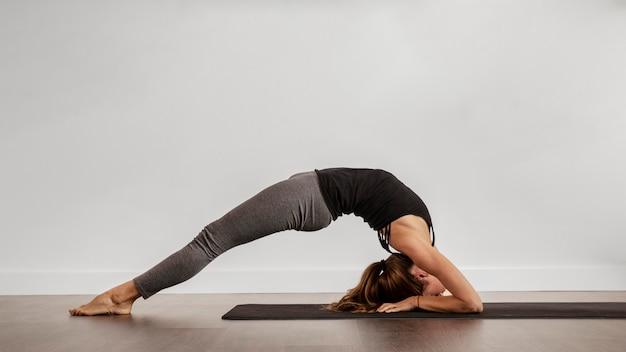 Dopasowana kobieta robi joga w domu