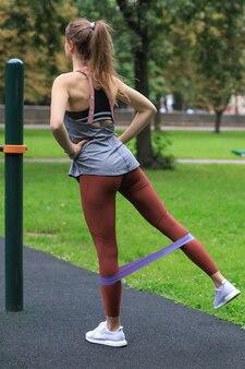 Dopasowana kobieta robi trening na świeżym powietrzu na boisku sportowym. huśtawka z gumową taśmą.