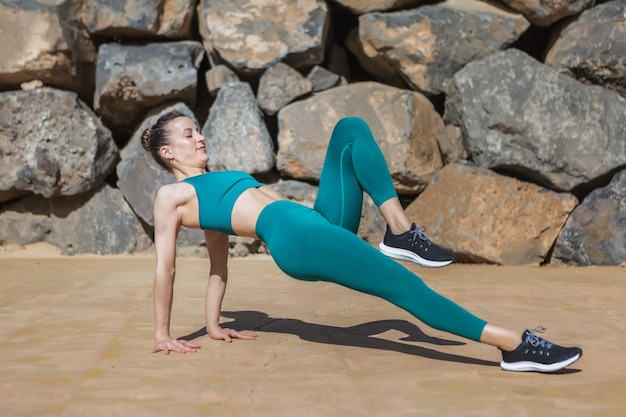 Dopasowana kobieta robi upward plank z uniesionym kolanem