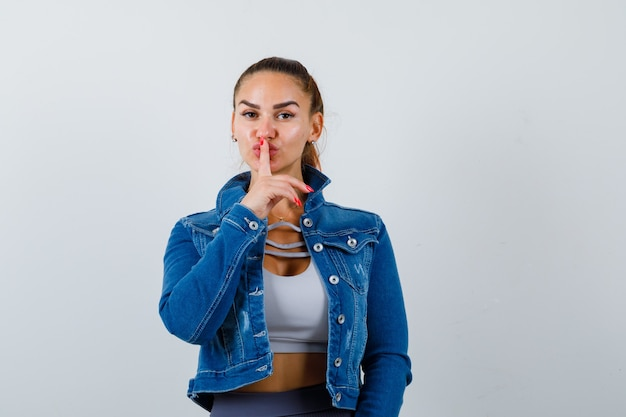 Dopasowana kobieta w crop top, dżinsowa kurtka, legginsy pokazujące gest ciszy i wyglądające poważnie, widok z przodu.