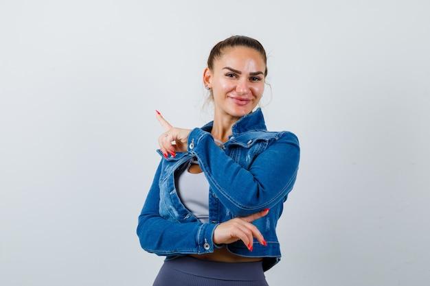 Dopasowana kobieta w crop top, dżinsowa kurtka, legginsy wskazujące w lewo i w prawo z palcami wskazującymi i patrząc wesoło, widok z przodu.